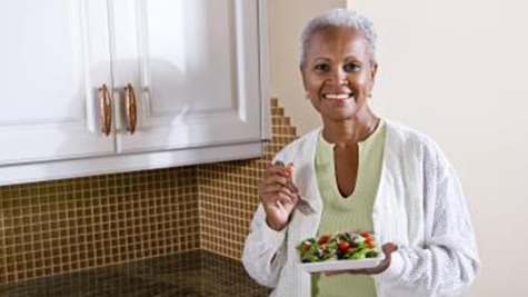older woman eats a salad while smiling