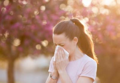 Woman with Allergies blows nose