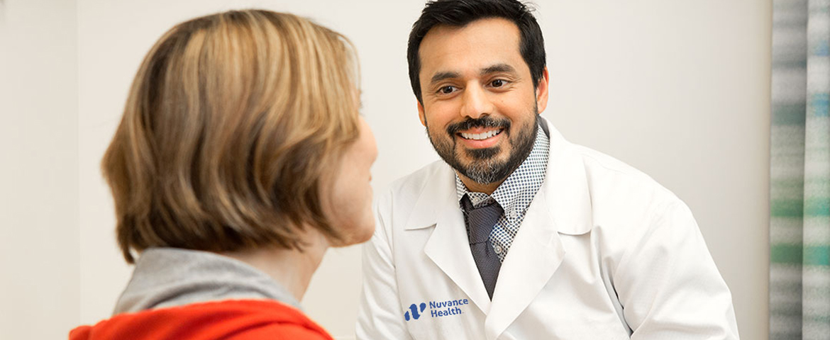 male doctor happily talks to patient